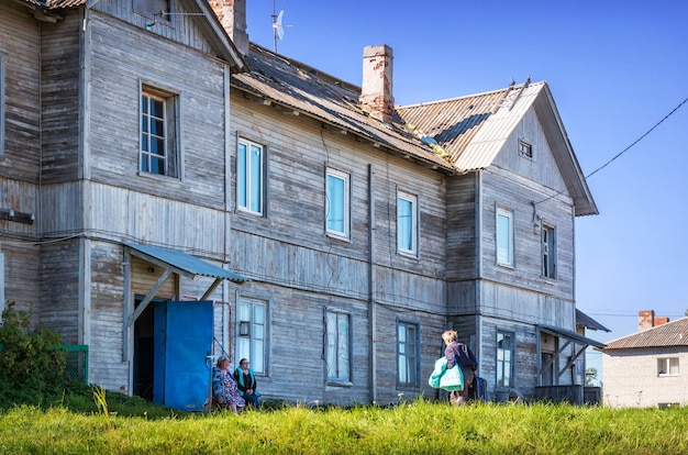 Solovetsky 섬의 지역 주민들은 마을의 목조 2 층 집 근처 벤치에 앉아 있습니다.