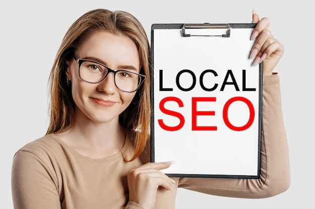 Local seo. beautiful young business woman wearing glasses holds a clipboard with mock up space isolated on gray background
