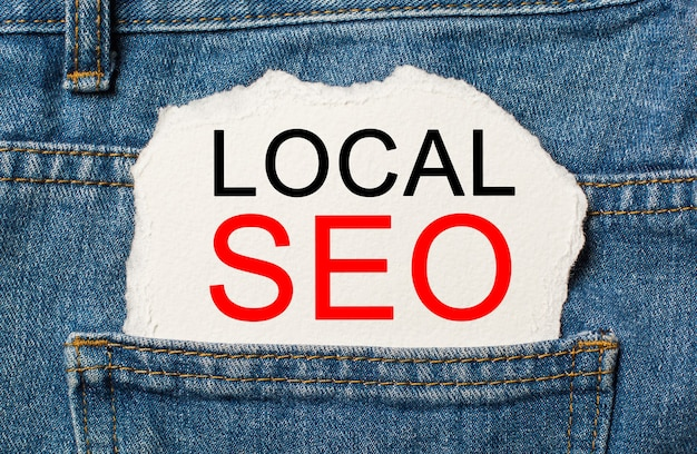 Local seo on torn paper background on jeans business and finance concept