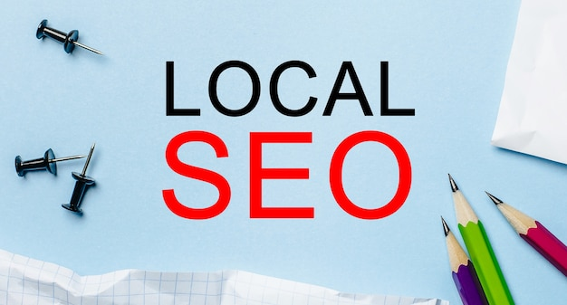Local seo on a white notepad with pencils on a blue background. business concept