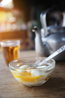 地元のタイの朝の食べ物の熱いお茶、木の背景に半熟卵