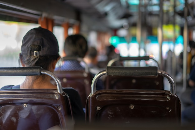Местный тайский пассажир сидит на сиденье кондиционированного автобуса бангкока для путешествия по бангкоку, таиланд.