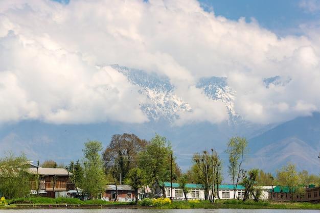 Local village mountain background along the border of dal lake in srinagar, kashmir, india