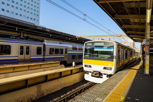 Local yellow and blue line jr trains on platform to pick up passengers in tokyo, japan