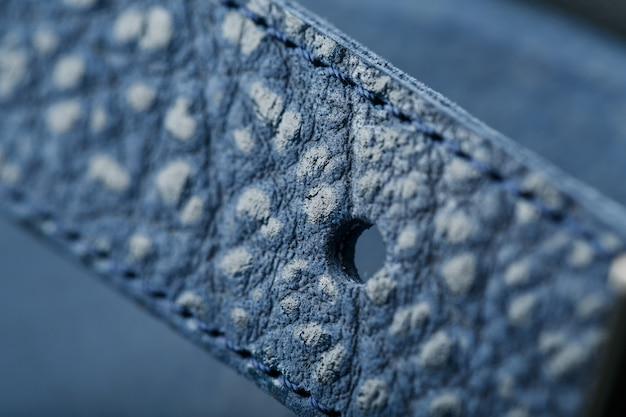 Замок и пряжка крупным планом, элементы синего рюкзака из натуральной кожи на темном