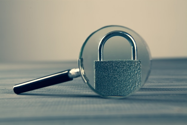 灰色の木製テーブルのロックと拡大鏡。検索セキュリティの概念