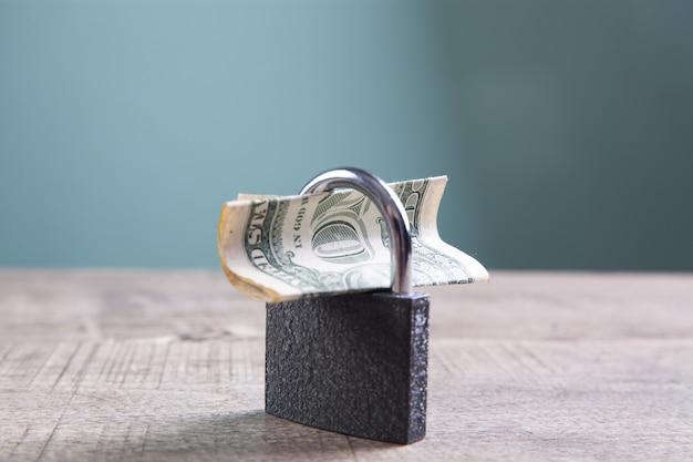 Замок и деньги на столе. блокировка денег