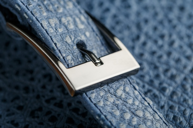 Lock and buckle close-up, elements of a blue backpack made of genuine leather on dark
