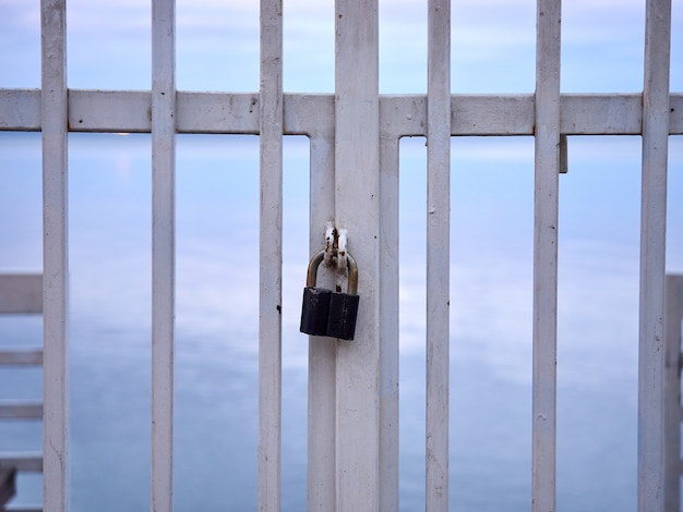 Lock on a metal white handrail fence against the sea