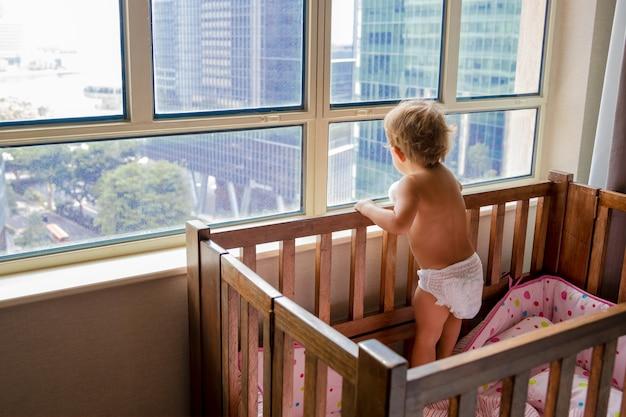 잠금 개념입니다. 유아용 침대에서 창 밖을 내다보는 대도시 거리...