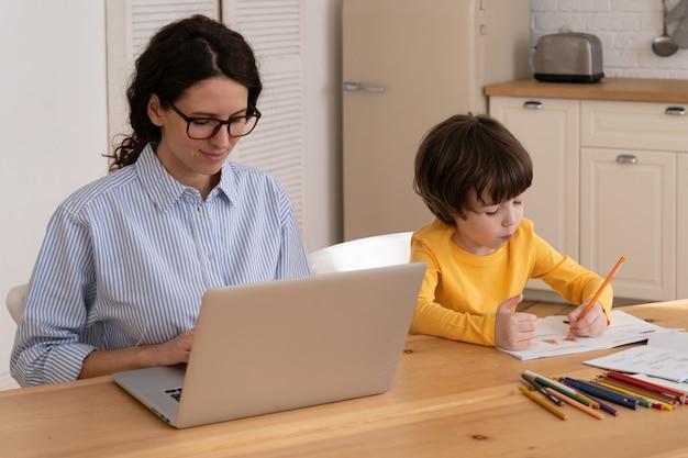 Запретная семья, удаленная работа, ребенок рисует, пока его мать работает на ноутбуке в домашнем офисе