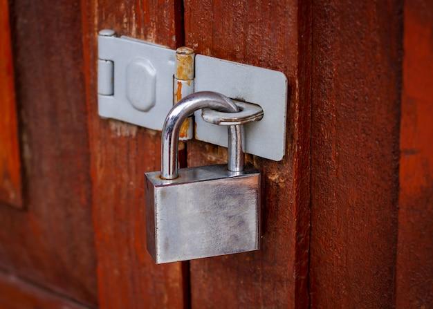 갈색 나무로되는 문에 체인 잠긴 된 자물쇠
