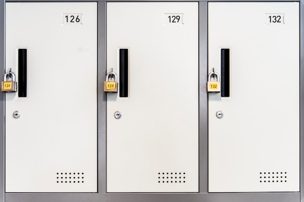 Locked white lockers with padlocks