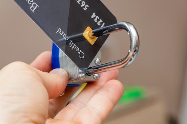 金属製の南京錠でロックされたプラスチック製のクレジットカードのクローズアップ