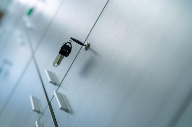 Шкафчик с ключом в офисной комнате. замок картотеки с ключом для системы безопасности в общественном объекте. система надежной блокировки файлов документов в офисе. белая дверь шкафчика для хранения.
