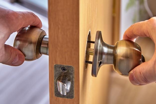 Слесарь собирает механизм дверной ручки с открытыми установочными винтами.