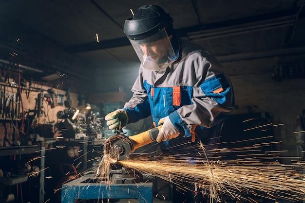 특수 옷과 고글의 자물쇠 제조공은 생산에서 일합니다. 앵글 그라인더로 금속 가공. 금속 가공에서 불꽃이납니다.