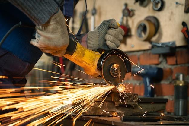 На производстве работает слесарь в спецодежде и защитных очках. обработка металла угловой шлифовальной машиной