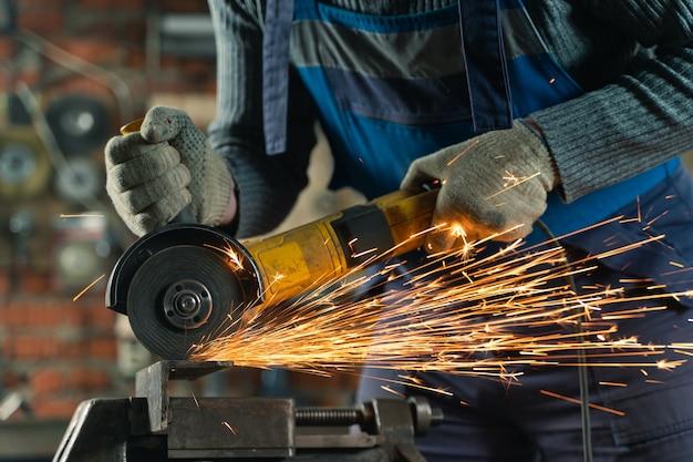特別な服とゴーグルの錠前屋は、アングルグラインダーを使用した生産金属加工で動作します
