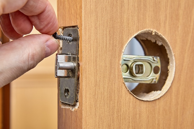 Слесарь устанавливает дверную ручку с замком.