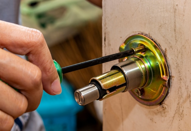 The locksmith is repairing the wooden door knob with screwdriver.