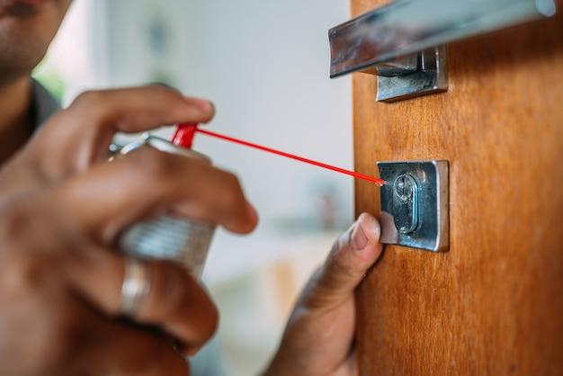 Слесарь открывает дверь. нанесение антиоксидантного спрея