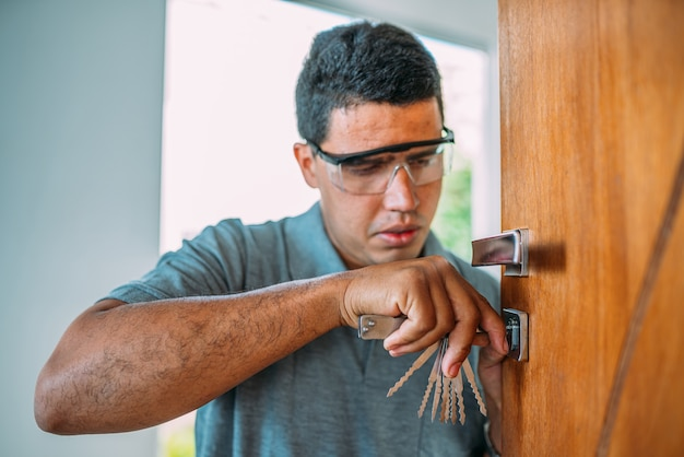Слесарь открывает дверь мужские руки ремонтируют или устанавливают металлический дверной замок с помощью отвертки