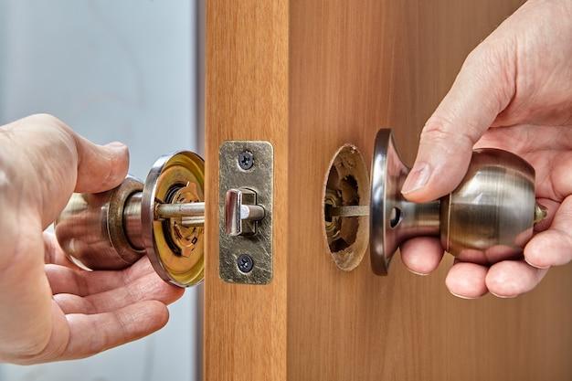 Слесарь показывает детали внутренней дверной ручки, включая ручку, розетку, засов, узел защелки, стержень и кнопку блокировки.