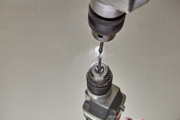 Locksmith는 거울에 구멍을 뚫는 동안 유리에 평평한 드릴 비트를 사용합니다.