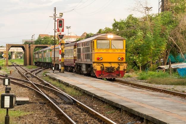 Локомотивный поезд по железнодорожным путям из таиланда заходит на вокзал. транспорт доставляет пассажира на вокзал. железнодорожные пути на крупном вокзале. традиционный транспорт.