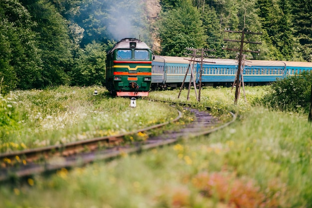 Locomotive with wagons riding railroad in carpathian mountains. train with passengers turning on railway. travel and tourism concept.