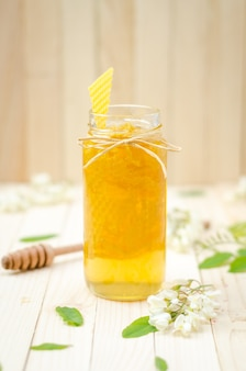 Locust honey in jar with locust blossoms on retro wooden table. close-up