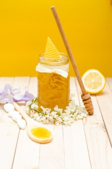Locust honey retro jar with locust blossoms and lemon on retro wooden table with honeycomb