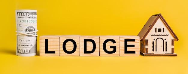 黄色の背景に家のミニチュアモデルとお金のあるロッジ。ビジネス、金融、クレジット、税、不動産、住宅、住宅の概念