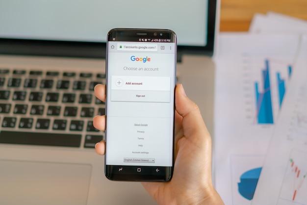 Loei, thailand - 10 мая 2017 года. рука samsung s8 с мобильным приложением для google на экране.