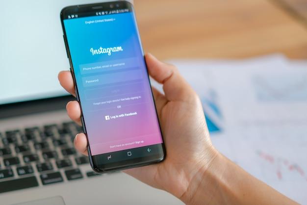 Loei, thailand - 10 мая 2017 года. рука samsung s8 с мобильным приложением для instagram на экране.