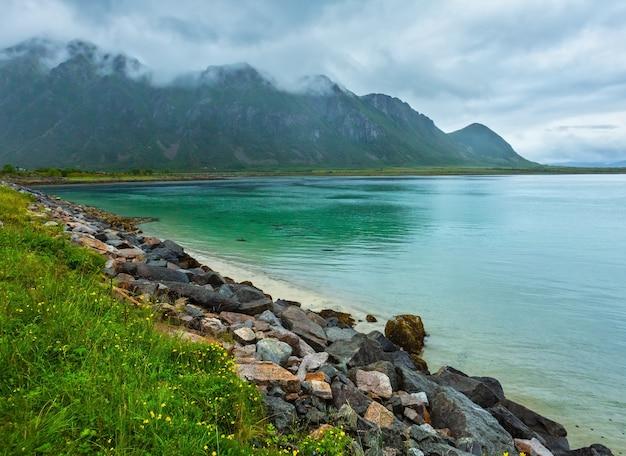 ロフォーテン諸島のフィヨルドと湖は、砂浜、湖、山々(ノルウェー)のある曇りの風景です。夏の極地の昼夜の眺め。