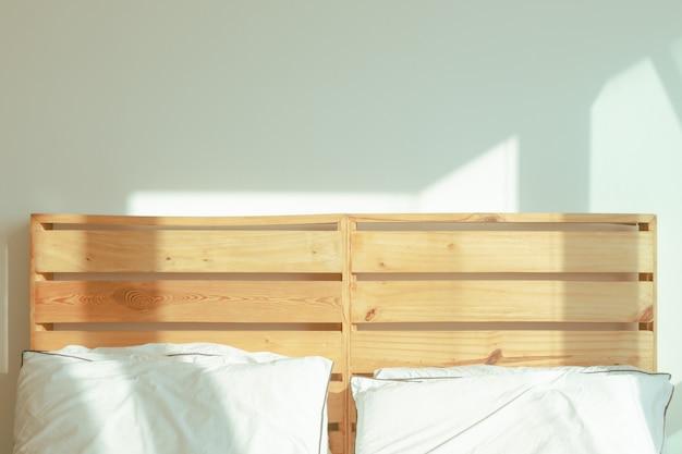 Спальня-лофт с белой кроватью в мягком солнечном свете зимнего утра.