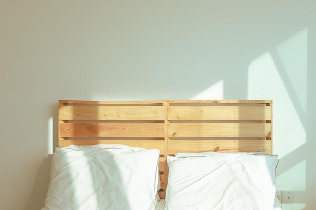 겨울 아침의 부드러운 햇빛에 흰색 침대가있는 로프트 침실.