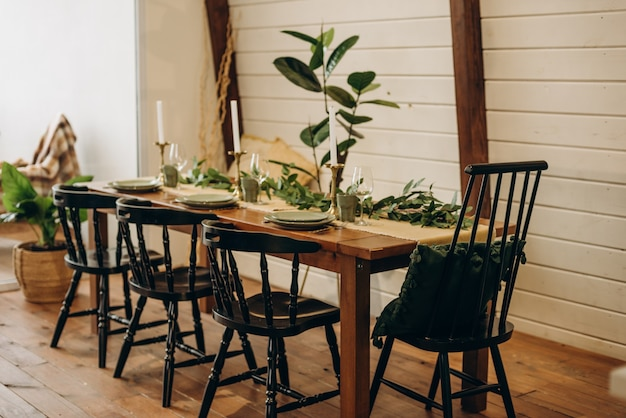 The loft dining table is decorated with flowers, candles and herbs. soft selective focus.