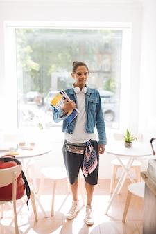 ロフトインテリア。大学卒業後にコーヒーを飲みに行く間本を持っているハンサムなブルネットの男