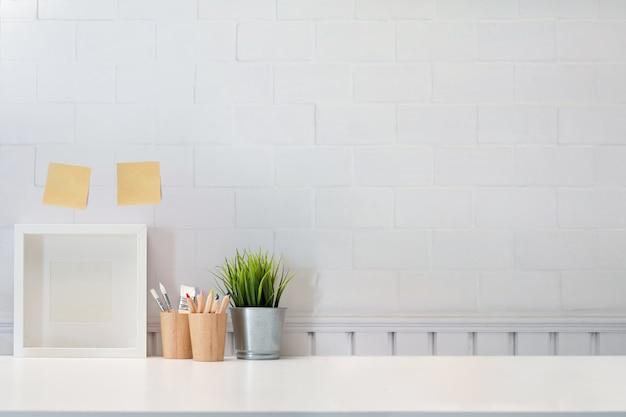 로프트는 흰색 테이블과 포스터 프레임, 책상에 최소한의 물건을 조롱합니다.