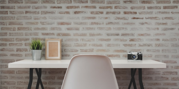 Loft modern workplace with white wooden table with office supplies and copy space with brick wall
