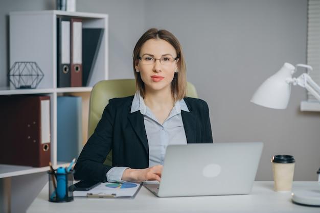 Молодая красивая брюнетка работает на ноутбуке в крутом креативном агентстве loft office.