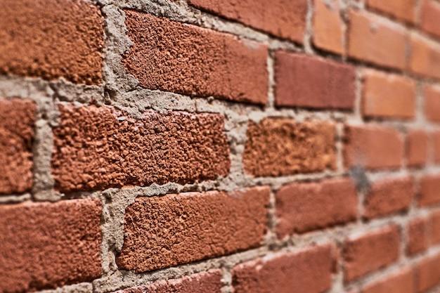 ロフト赤レンガの壁、角度の付いたビュー。屋根裏部屋の内部の磨かれたレンガの壁