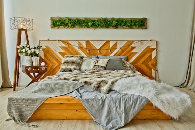 グレーとブラウンのロフトスタイルのベッドルームとたくさん。灰色の羽毛布団と毛皮の毛布付きのベッド。