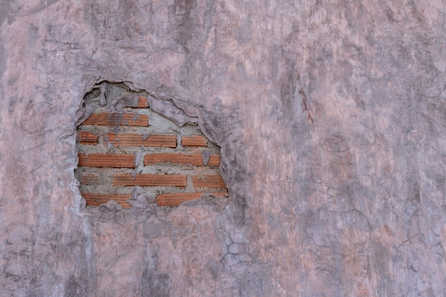 Loft style cement wall with crack and orange brick