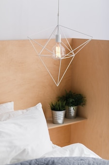 Loft style geometric white ceiling lamp with light wooden background and an edison bulb.
