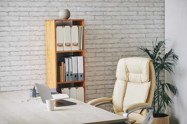 Loft-style office with laptop sitting on desk, executive chair and document folders on shelves