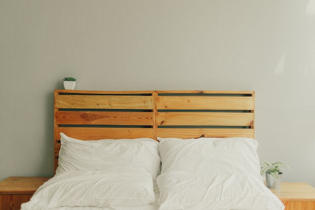 Loft wooden pine headboard with white bed.